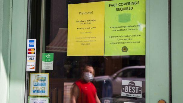 PHOTO: A pedestrian passes in front of a sign that reads 'Face Coverings Required' outside a store in downtown Concord, N.H., Sept. 14, 2020. (Bloomberg via Getty Images, FILE)