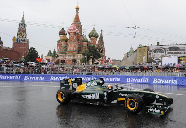 """Formula One Team Lotus driver Karun Chandhok of India drives past St. Basils cathedral during the """"Moscow City Racing"""" show on July 17, 2011 in central Moscow. AFP PHOTO / NATALIA KOLESNIKOVA (Photo credit should read NATALIA KOLESNIKOVA/AFP/Getty Images)"""