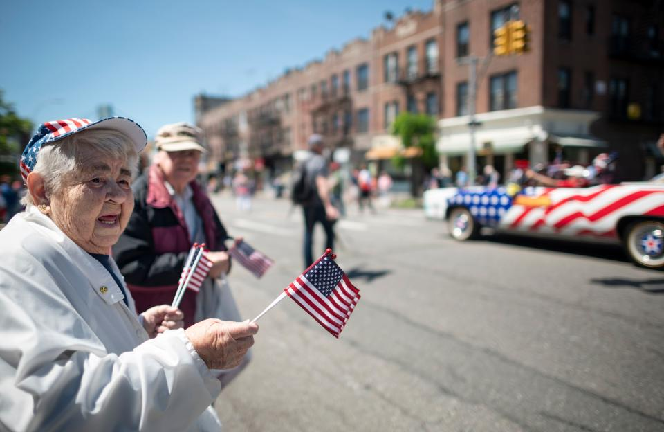An elderly woman waves American flags to veterans as they march on the street in Brooklyn. (Photo: JOHANNES EISELE/AFP via Getty Images)