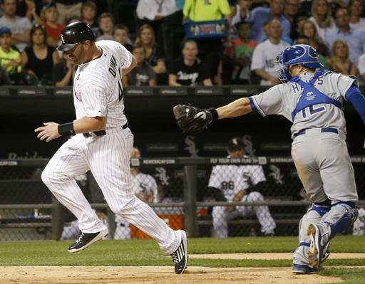 Chicago White Sox's Adam Dunn scores past Kansas City Royals catcher Brett Hayes (12) on a sacrifice fly by Gordon Beckham to center fielder Lorenzo Cain, during the sixth inning of a baseball game Monday, July 21, 2014, in Chicago. (AP Photo/Charles Rex Arbogast)