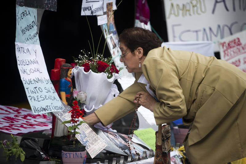 A supporter of Argentina's President Cristina Fernandez places flowers outside the Favaloro Hospital in Buenos Aires, Argentina, Wednesday, Oct. 9, 2013. The doctors who removed a blood clot from the brain of Argentina's president on Tuesday say she's improving without complications. (AP Photo/Victor R. Caivano)