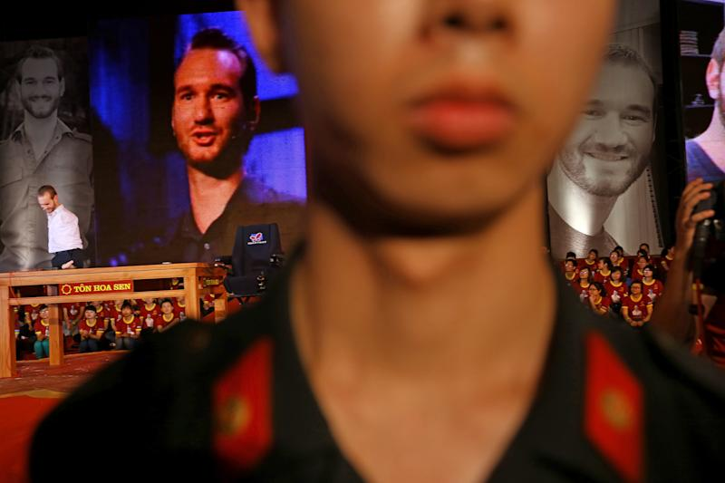 In this Thursday, May 23, 2013 photo, a Vietnamese policeman guards while Nick Vujicic, a Serbian Australian evangelist who was born with no limbs, left, gives his speech to a crowd of about 25,000 students and young people at My Dinh national stadium in Hanoi, Vietnam. Vujicic, who is able to stand up and move around on his pelvis, shuffled round on a small table set up on a stage on corner of the field. In a talk laced with jokes, platitudes and attempts at Vietnamese, he spoke out against bullying and drinking; on the need for forgiveness and hope; and respect for family. All those themes resonate with Vietnamese and their leaders, one of whom - the vice president - was watching from the VIP area. (AP Photo/Na Son Nguyen)