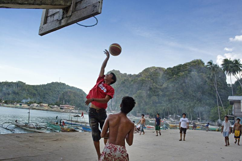 FILE PHOTO: At a fishing village in El Nido, Palawan, the Philippines, young men play basketball at the end of their work day. (Photo by Jonas Gratzer/LightRocket via Getty Images)