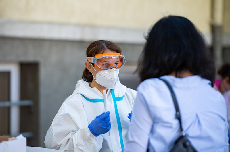 25 June 2020, North Rhine-Westphalia, Oelde: A member of the Bundeswehr takes a smear test on a woman at a corona smear site in Oelde. Because of the corona outbreak at the meat producer Tönnies in Rheda-Wiedenbrück, many people from the area cannot easily escape on holiday: In several popular regions at home and abroad, negative tests are being demanded of them. Photo: Guido Kirchner/dpa (Photo by Guido Kirchner/picture alliance via Getty Images)