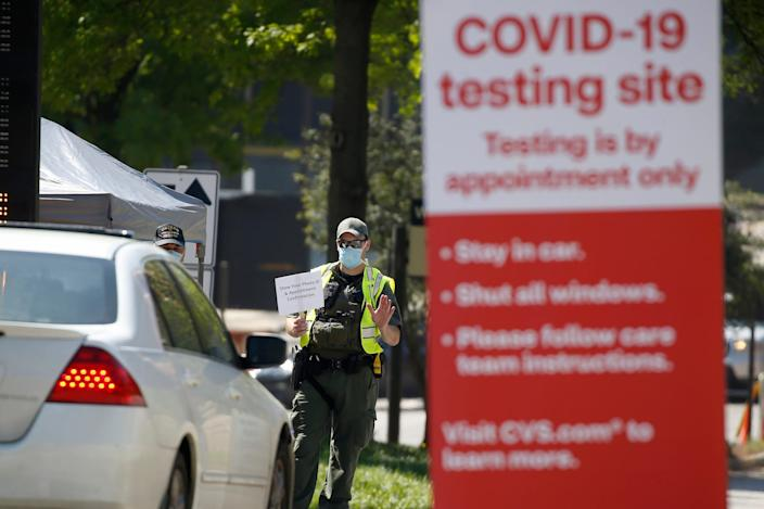 A police officer directs cars into a coronavirus testing facility at Georgia Tech Monday, April 6, 2020, in Atlanta.