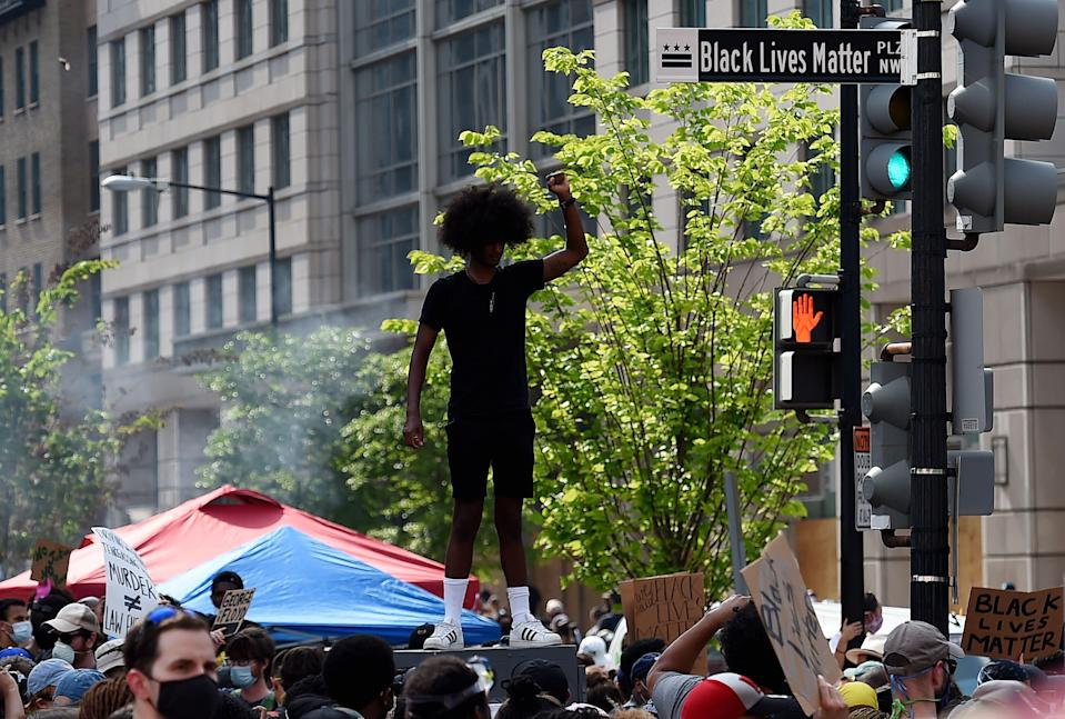 """A demonstrator holds up his fist near a street sign that has been renamed """"Black Lives Matter Plaza"""" near the White House during a peaceful protest against police brutality and racism, on June 6, 2020 in Washington, D.C."""