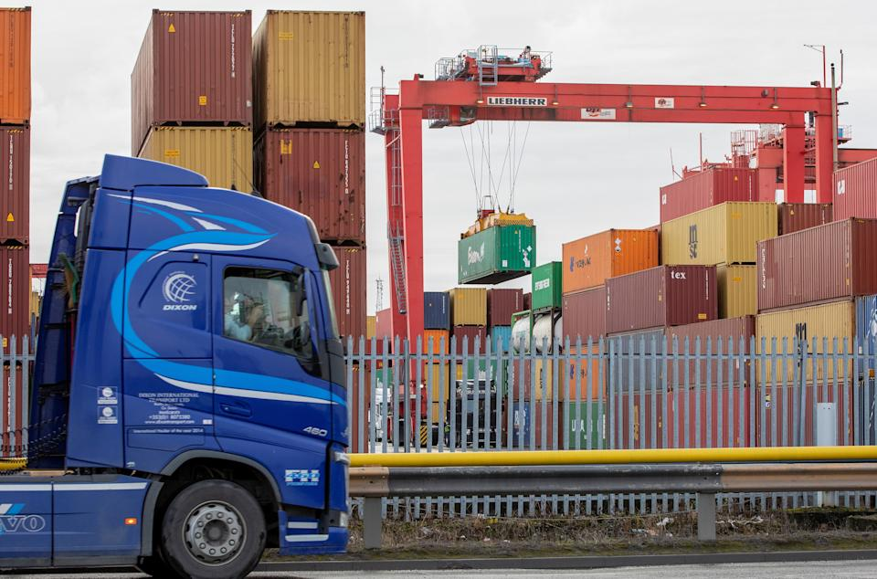 """Shipping containers are pictured as a freight lorry or heavy goods vehicle (HGV) leaves from Dublin Port in Dublin, Ireland on January 12, 2021. - Northern Ireland's supply chain is """"within days of falling apart"""" as new post-Brexit checks stem the flow of freight into the UK province, hauliers warned on Monday. Supermarkets are """"experiencing considerable difficulties"""" stocking shelves since the Brexit transition period ended, said Road Haulage Association (RHA) policy manager for Northern Ireland John Martin. (Photo by PAUL FAITH / AFP) (Photo by PAUL FAITH/AFP via Getty Images)"""