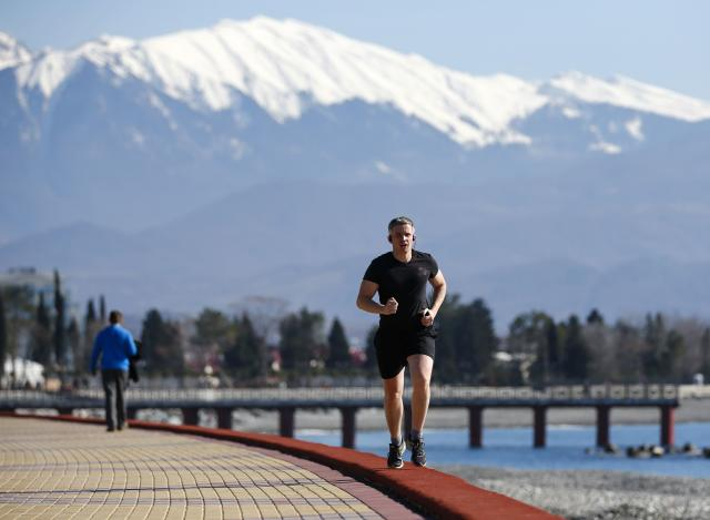 A man jogs along the coast on a sunny day near the Olympic Park during the 2014 Sochi Winter Olympics February 12, 2014. REUTERS/Shamil Zhumatov (RUSSIA - Tags: SPORT OLYMPICS ENVIRONMENT)