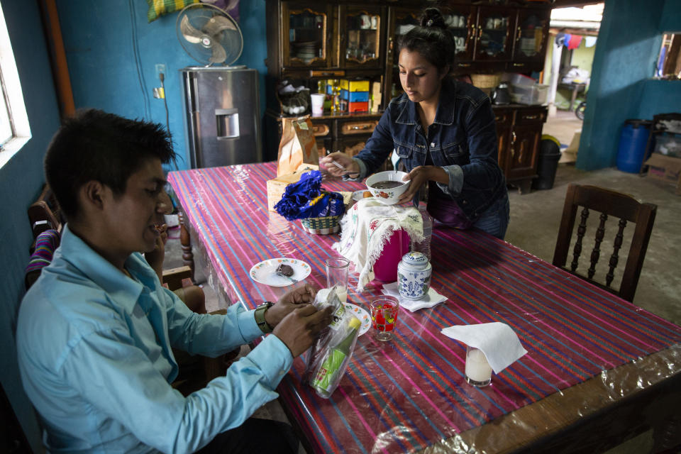 """Teacher Gerardo Ixcoy and his wife Yessika Lopez prepare to have lunch in their home in Santa Cruz del Quiche, Guatemala, Wednesday, July 15, 2020. """"One day the mother of a student told me they didn't have food,"""" Ixcoy said. """"When class ended and I began to ride away on my tricycle she calls me and with a look of gratefulness says, 'Teacher, they gave me some food, I want to share half with you.'"""" (AP Photo/Moises Castillo)"""