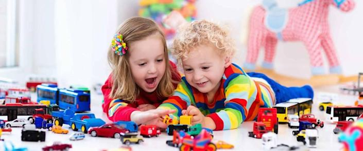 Little toddler boy and girl playing with model car collection on the floor.