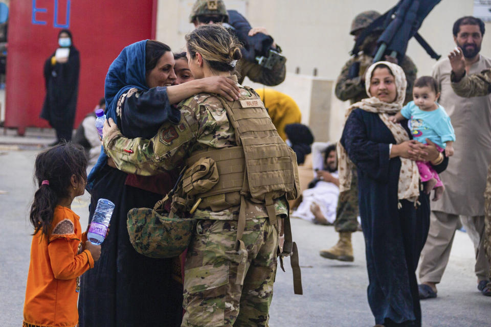 In this image provided by the U.S. Marines, a U.S. Airman with the Joint Task Force-Crisis Response embraces a mother after helping reunite their family at Hamid Karzai International Airport in Kabul, Afghanistan, Friday, Aug. 20, 2021. (Cpl. Davis Harris/U.S. Marine Corps via AP)