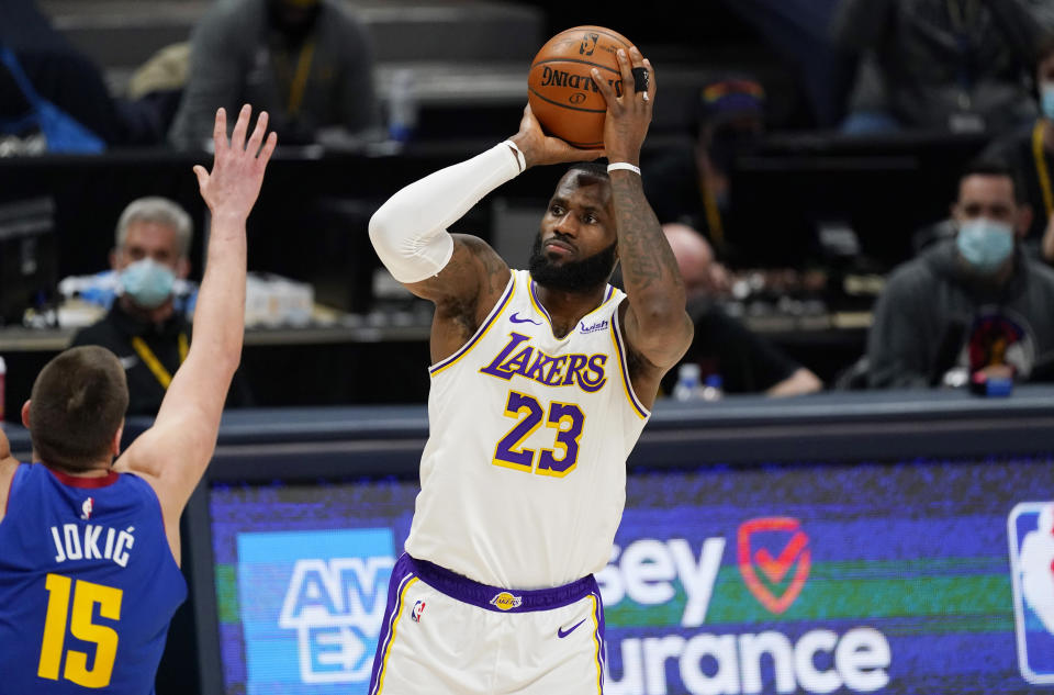 LeBron James with the ball in his hands in a shooting motion above his head as Nikola Jokic holds up a hand to defend in front.