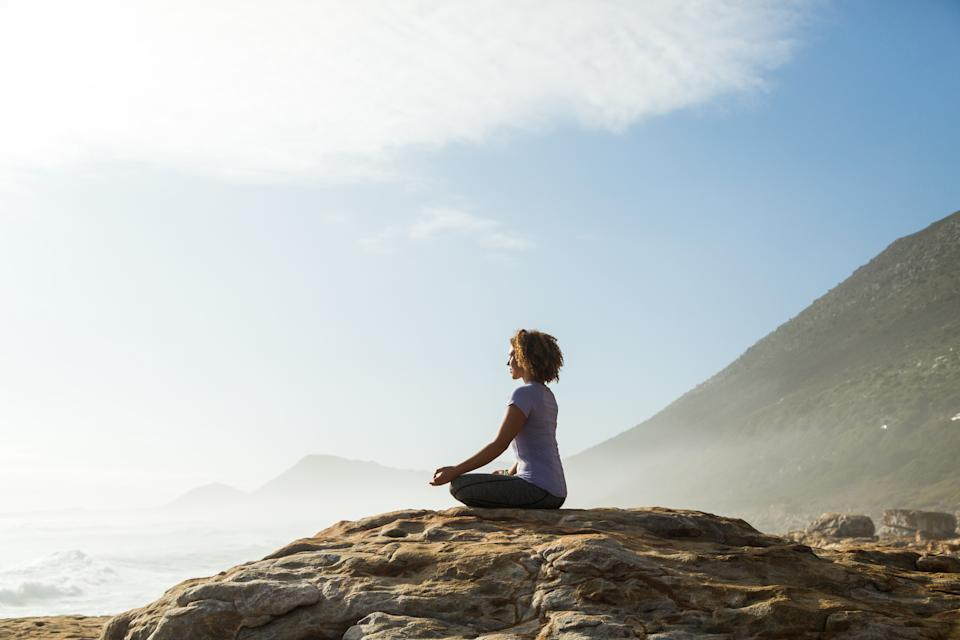 A woman meditating on top of a rock overlooking the ocean.