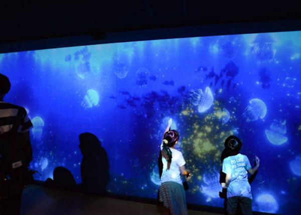 ▲ Interactive images are projected on the walls of the passageway. Touching an image of a jellyfish causes stars to sparkle and sound to be played.