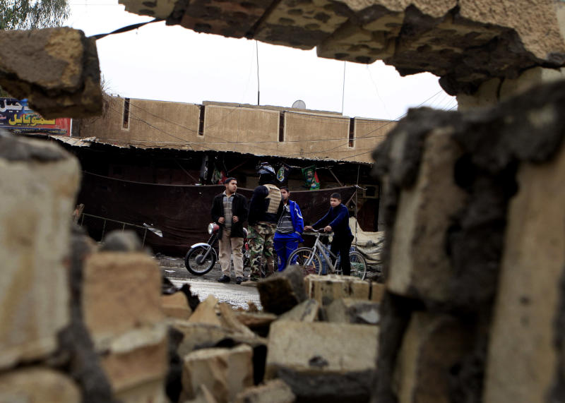 Iraqi's are seen through broken bricks of a damaged mosque after a car bomb attack in Dujail, 80 kilometers (50 miles) north of Baghdad, Iraq, Thursday, Jan. 17, 2013. Insurgents unleashed a string of bomb attacks mainly targeting Shiite Muslim pilgrims across Iraq on Thursday, killing and wounding scores of people, police said. (AP Photo/ Karim Kadim)