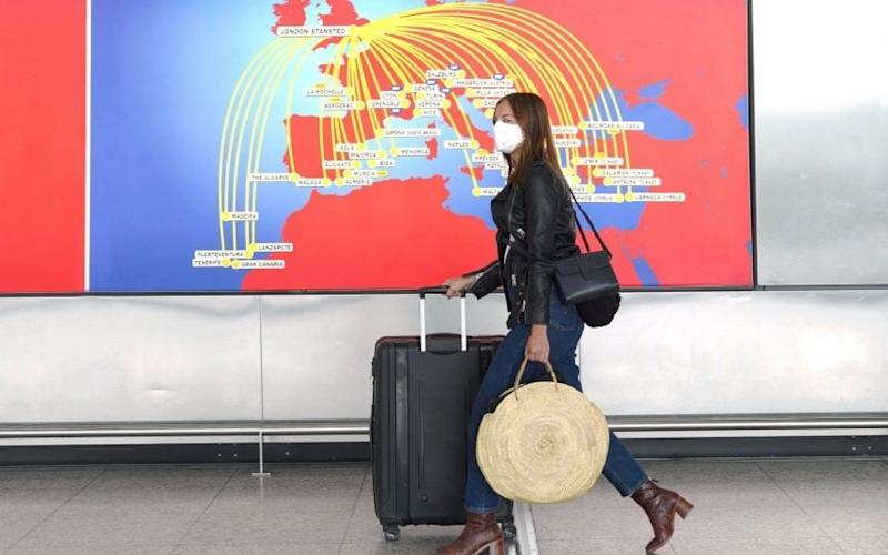 Holiday-ready? An air passenger passes through Stansted Airport today.CREDIT: ALAMY - Alamy