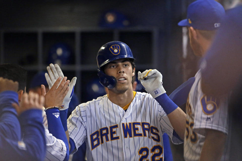 Milwaukee Brewers' Christian Yelich is congratulated in the dugout after hitting a solo home run during the third inning of the team's baseball game against the Philadelphia Phillies on Friday, May 24, 2019, in Milwaukee. (AP Photo/Aaron Gash)