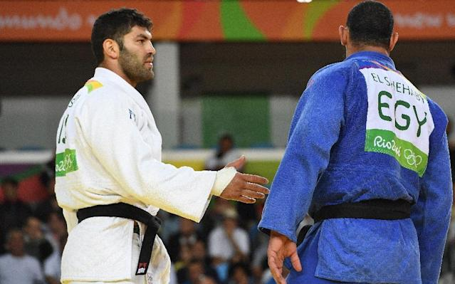 Israel's Or Sasson (white) competes with Egypt's Islam Elshehaby during their men's +100kg judo contest match of the Rio 2016 Olympic Games in Rio de Janeiro on August 12, 2016. (AFP Photo/Toshifumi KITAMURA)