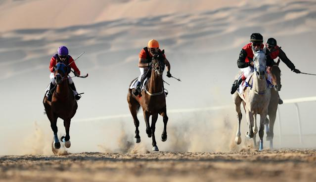 <p>Jockeys on purebred Arab horses race during the 2018 Moreeb Dune Festival on Jan. 1 in the Liwa desert, some 250 kilometers west of Abu Dhabi. (Photo: Karim Sahib/AFP/Getty Images) </p>
