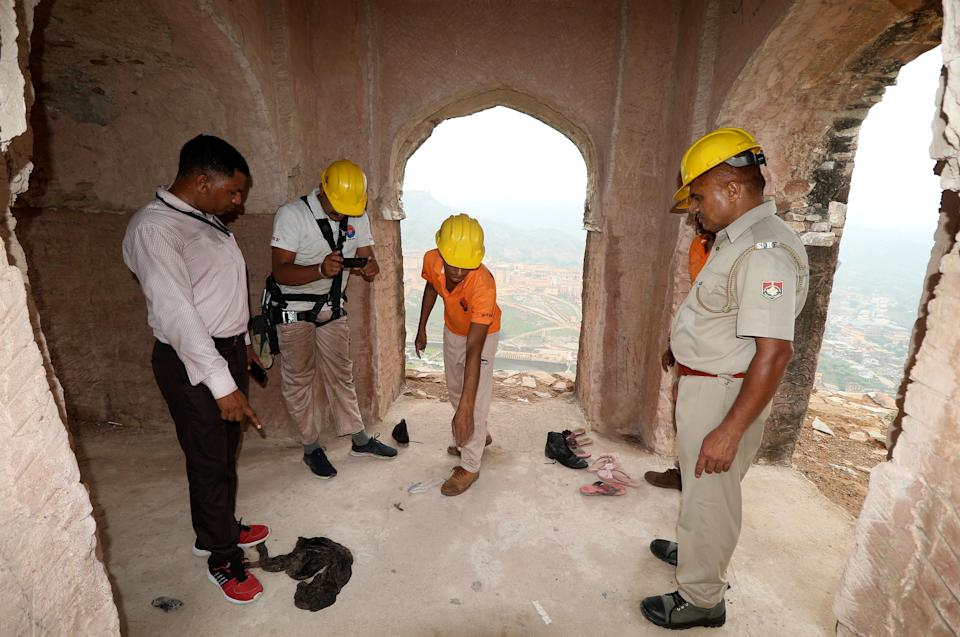 Members of the State Disaster Response Force (SDRF) examine the site following a lightning strike at a watch tower near Amer Fort in Jaipur in the desert state of Rajasthan, India, July 12, 2021. REUTERS/Stringer NO ARCHIVES. NO RESALES.