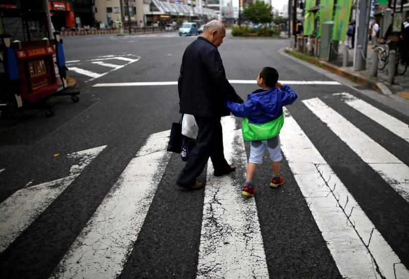A man and his grandchild walk on the street at Tokyo's Sugamo district