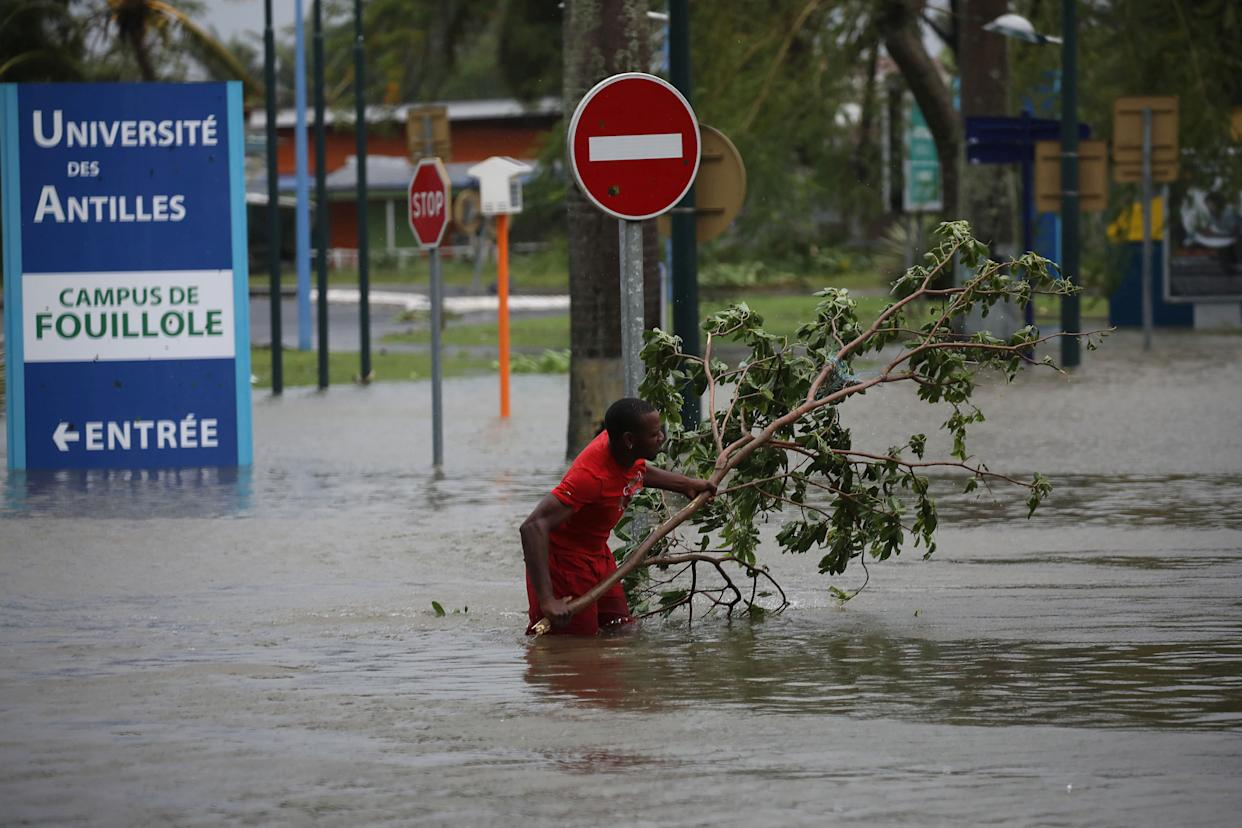 A man removes a branch in a flooded street in Pointe-a-Pitre, on the French island of Guadeloupe on Sept. 19, 2017, after the passage of Hurricane Maria.