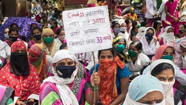 A protesting ASHA worker with a placard that reads,
