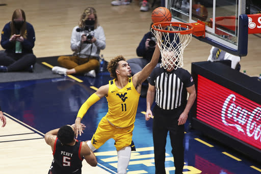 West Virginia forward Emmitt Matthews Jr. (11) shoots while defended by Texas Tech guard Micah Peavy (5) during the second half of an NCAA college basketball game Monday, Jan. 25, 2021, in Morgantown, W.Va. (AP Photo/Kathleen Batten)
