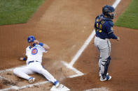 Chicago Cubs' Nico Hoerner, left, slides across homeplate scoring a run on a fielders choice as Milwaukee Brewers catcher Omar Narvaez, right, looks on during the first inning of a baseball game in Chicago, on Thursday, Aug. 13, 2020. (AP Photo/Jeff Haynes)