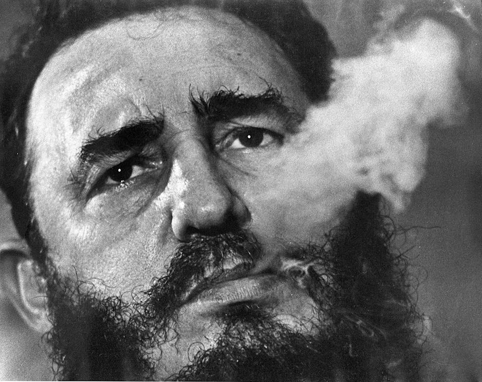 <p>Cuban Prime Minister Fidel Castro exhales cigar smoke during a March, 1985 interview at his presidential palace in Havana. Castro, a Havana attorney who fought for the poor, overthrew dictator Fulgencio Batista's government on Jan. 1, 1959. He defeated a U.S. attempt, known as The Bay of Pigs invasion, to overthrow his revolutionary regime on April 19, 1961. Afterwards, Cuba armed itself with Soviet nuclear missiles aimed at the United States which almost brought the world to the brink of nuclear disaster. Castro's communist regime still exists in Cuba, 90 miles from the U.S., at the close of the 20th century. (AP Photo/Charles Tasnadi) </p>