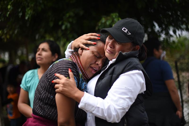 Women cry outside a provisional morgue in the village of El Cambray II, some 15 km east of Guatemala City, on October 3, 2015 after a landslide (AFP Photo/Johan Ordonez)
