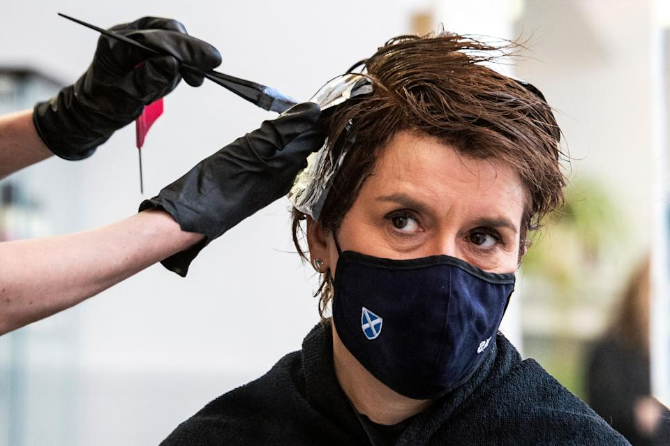 Scotland's first minister Nicola Sturgeon, wearing a face covering, is reflected in a mirror as she has her hair coloured and cut at Beehive Hair and Make up hairdressers' salon in Edinburgh on 5 April. Photo: Andy Buchanan/AFP via Getty Images