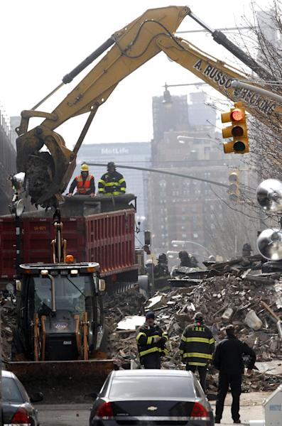 Debris is removed from a mound of rubble a day after a gas leak-triggered explosion, Thursday, March 13, 2014, in East Harlem, New York. Rescuers working amid gusty winds, cold temperatures and billowing smoke pulled additional bodies Thursday from the rubble of two apartment buildings that collapsed Wednesday. (AP Photo/Julio Cortez)