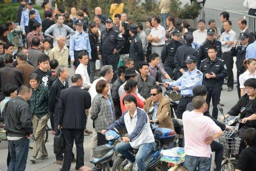 <p>Residents are seen gathering outside the city government offices in Ningbo, in eastern China's Zhejiang province on October 29, as police and security personnel look on. Authorities in Ningbo said late Sunday that work on the 55.9-billion-yuan ($8.9 bln) oil refining and petrochemical complex would be called off after thousands of locals clashed with police in a week-long protest.</p>