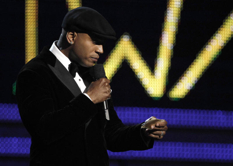 """FILE - This Feb. 12, 2012 file photo shows LL Cool J reciting a prayer for the late Whitney Houston at the 54th annual Grammy Awards in Los Angeles. Host LL Cool J said addressing the Grammy audience at Staples Center after Houston's death was """"definitely the most challenging moment I've faced in my career."""" This and other last-minute changes made to the 54th annual Grammy Awards are chronicled in a new documentary, """"A Death in the Family: The Show Must Go On,"""" which premiered Monday at the Academy of Television Arts and Sciences. (AP Photo/Matt Sayles, file)"""