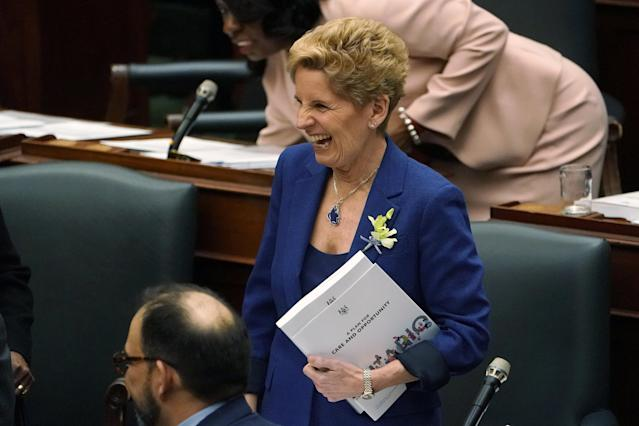 Ontario Premier Kathleen Wynne laughs as she walks with a copy of the new provincial budget under her arm at Queen's Park in Toronto, Ontario, Canada, March 28, 2018. REUTERS/Carlo Allegri