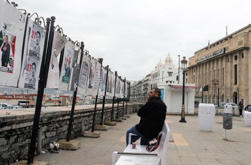Man sits in front of parliamentary election campaign posters in Algiers