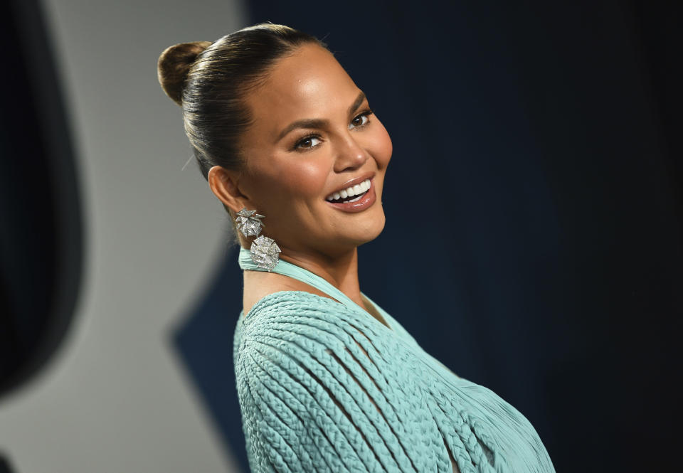 """FILE - Chrissy Teigen arrives at the Vanity Fair Oscar Party on Feb. 9, 2020, in Beverly Hills, Calif. Teigen will grace the front of People magazine's """"The Beautiful Issue"""" in a cover story that delves into her evolved definition of beauty, facing racism growing up and her heartbreaking miscarriage last year. The magazine revealed the cover Wednesday, March 31, 2021, of the annual issue, which hits newsstands Friday. (Photo by Evan Agostini/Invision/AP, File)"""