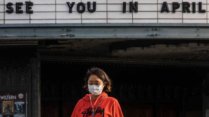 A woman walks wearing a mask to protect herself from the novel coronavirus (COVID-19) in front of a closed theater in Koreatown, Los Angeles, on March 21, 2020 (Photo: APU GOMES/AFP via Getty Images)