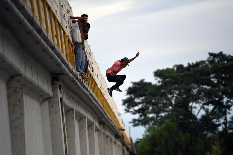 A Honduran migrant jumps to the Suchiate River from the Guatemala-Mexico international border bridge to swim and reach Mexico (AFP Photo/Pedro PARDO)