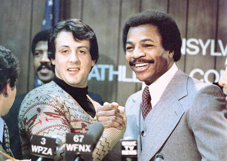 American actors Sylvester Stallone (L) and Carl Weathers grip hands and smile together during a press conference in a still from the film, 'Rocky,' directed by John G. Avildsen, 1976. (Photo by United Artists/Courtesy of Getty Images)
