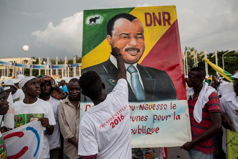 A man puts the last touches to a painting of incumbent Congolese President Denis Sassou Nguesso at the closing rally of his electoral campaign in Brazzaville (AFP Photo/Marco Longari)