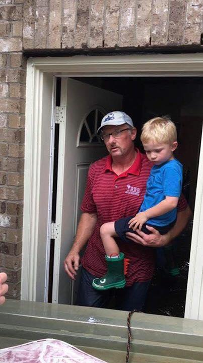 Beau Rawlins of Galveston helps rescue a child in a flooded home in the Dickinson area. (Photo: Courtesy of Beau Rawlins.)