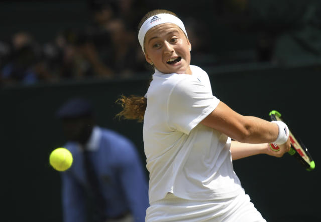 Jelena Ostapenko of Latvia returns the ball to Angelique Kerber of Germany during their women's semifinal match at the Wimbledon Tennis Championships in London, Thursday July 12, 2018. (Neil Hall/Pool via AP)