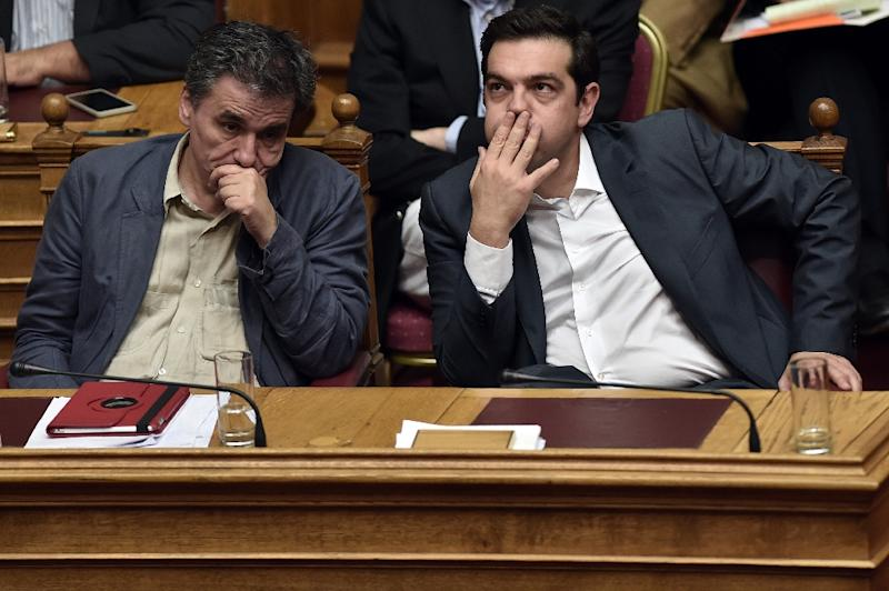 Running contrary to his promises to eliminate austerity once in power, the bailout has put major strain on Prime Minister Alexis Tsipras (R) (AFP Photo/Aris Messinis)