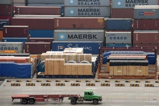 A truck drives past Maersk and COSCO containers at the deep-sea port of Shanghai in 2011