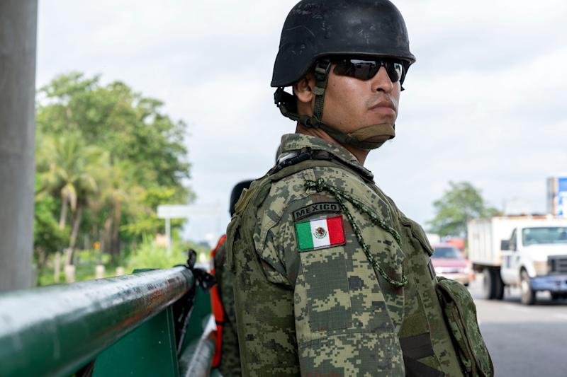 TAPACHULA, Mexico – A member of Mexico's National Guard stands watch as a Mexican immigration officer boards a bus headed north on the Pacific Coast Highway near Tapachula. In June, Mexico's President AndrésManuel LópezObrador, under pressure from the U.S., sent National Guard troops to help immigration authorities block migrants from Central America from reaching the U.S.