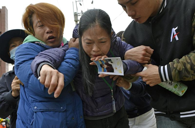 A mother holds a picture of her son after a male student body was recovered from the Wei-Kuan complex which collapsed in the 6.4 magnitude earthquake, in the southern Taiwanese city of Tainan on February 10, 2016 (AFP Photo/Sam Yeh)