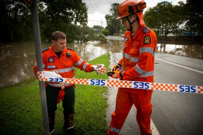 A State Emergency Service crew close off a flooded road in Beenleigh, noertheast Australia on March 31, 2017