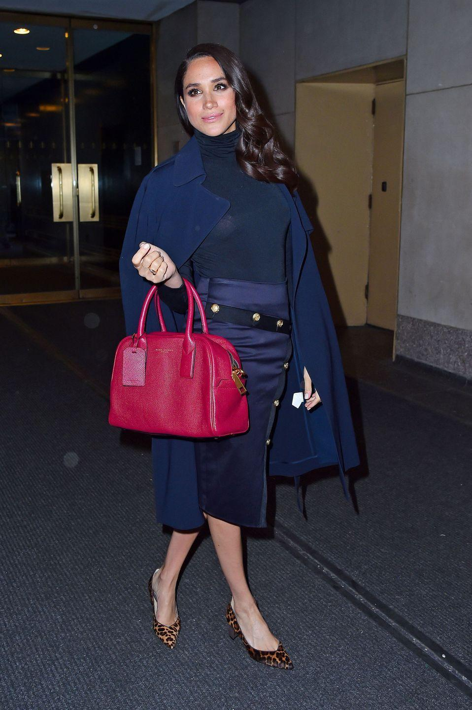 <p>Head to toe in navy, Meghan wears a skirt by Veronica Beard with popping pink Marc Jacobs bag at the 'Today Show', March 2016</p>